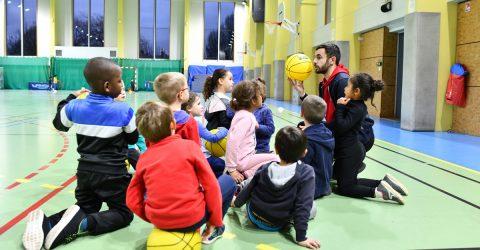 Enfants écoutant un cours de basket