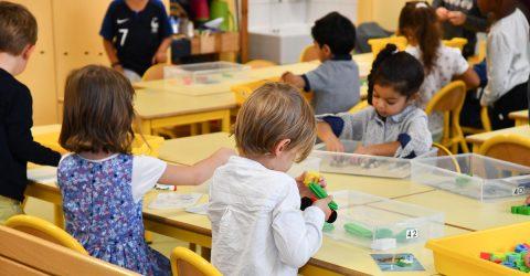 Enfants maternelle jouant sur des tables