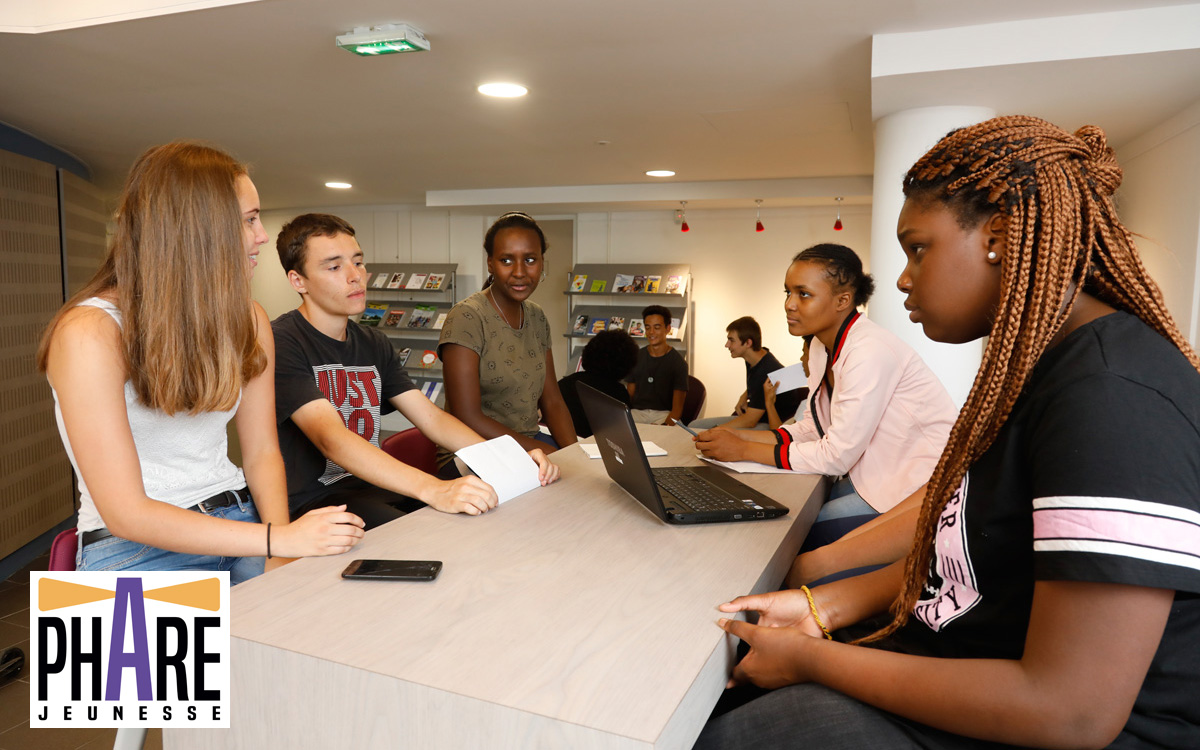 Jeunes autour d'une table au phare jeunesse + logo du Phare